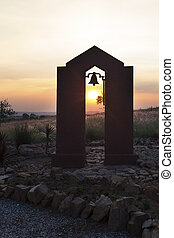 Silhouette at sunset of a bell in an arch