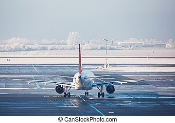 Airport in winter. Airplane is taxiing to the runway for...