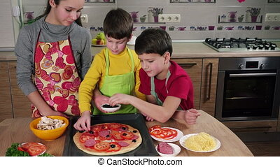 Three kids adding the olives to raw pizza on table in the...