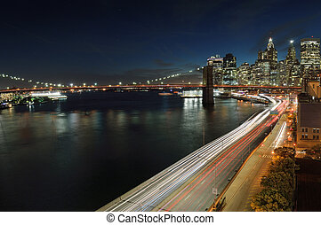 Brooklyn Bridge at night. - View of Lower Manhattan with...