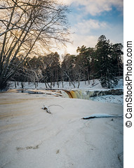 Partly frozen Keila-Joa waterfall by winter sunset, Estonia...