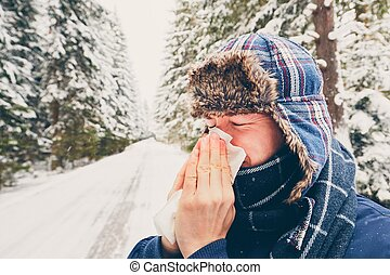 Ill man in winter nature - Ill man with paper tissue in...