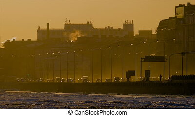 Beautiful view of the seafront in the mist, which going cars with lights at sunset. Saint-Petersburg, Russia
