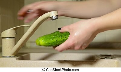 Hand are washed cucumber under running water. - Hand are...