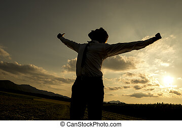 Person with spread arms in countryside sunset