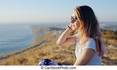 Beautiful girl with a sunglasses at the cliff above the sea?
