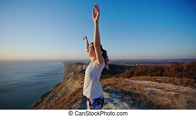 Girl standing on the cliff and raising her hands up