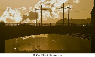 cars, trucks and buses cross the bridge in sunset time....
