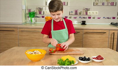 Adorable boy cutting the paprika in kitchen