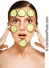 Freckles whitening - Young freckled woman with cucumber mask...