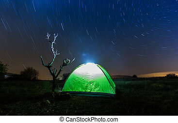 long exposure - A tent in the woods under a star filled sky.