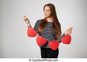 Smiling woman holding garland of four red paper hearts -...