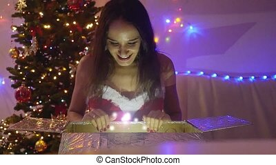 Young happy beautiful woman sits at the magical Christmas...
