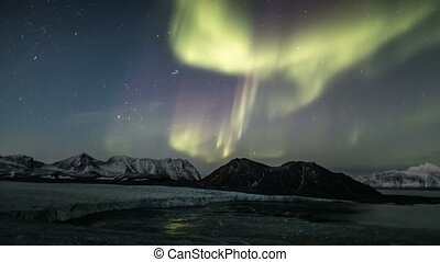 Northern lights over the Arctic fjord and glaciers