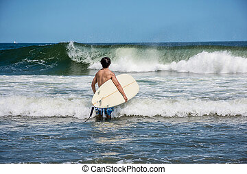 Ready to Surf - A surfer checks out the waves along the...