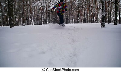 Man Walking in the Deep Snow in the Winter Forest at Snowy Day. Slow Motion