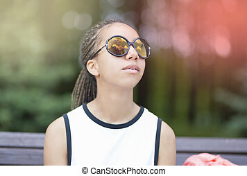 Portrait of African American Teenager With Long Dreadlocks Posing in Park Outdoors in Sunglasses