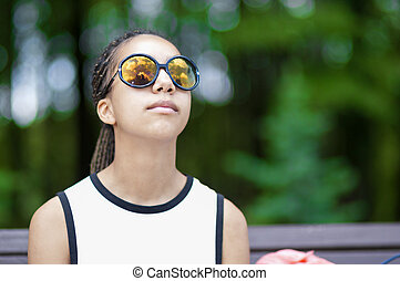 Natural Portrait of Tranquil African American Teenager With Long Dreadlocks Posing in Park Outdoors in Sunglasses