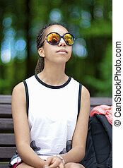 Natural Portrait of Tranquil African American Teenager With Long Dreadlocks Posing in Park Outdoors in Sunglasses.