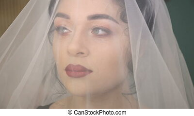 Face of the young beautiful bride under the white wedding veil