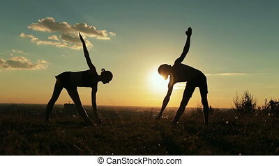 Silhouette of sporty man and woman doing triangle pose in the park at sunset