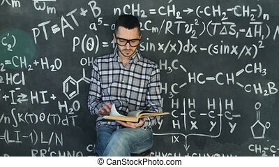 Young scientist man read book in chemical and mathematical...