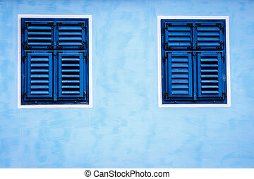 Window with blue shutters on a blue wall, close up