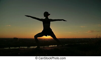 Woman doing Ashtanga yoga in the park at sunset - Silhouette...