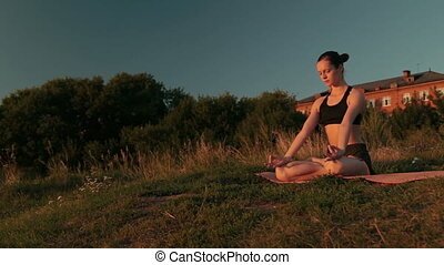 Sporty woman in lotus position in the park at sunset. Sunset...