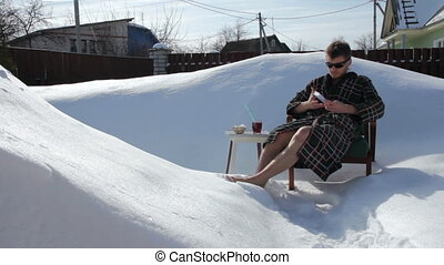 Young man is resting on the snow and drinking juice