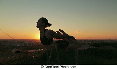 Woman practicing yoga in the park at sunset - Silhouette of...