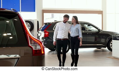 Couple walks at the car dealership - Young couple walking at...