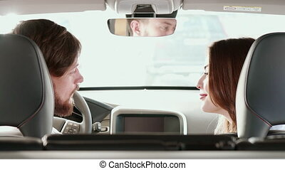 Couple turns their faces to the back seat inside the car -...