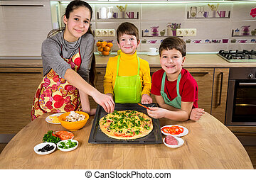 Three kids adding ingredients to raw pizza