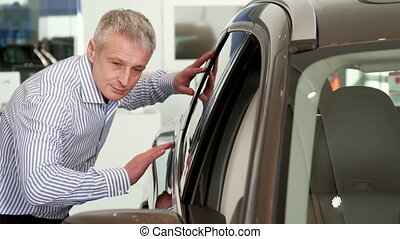 Mature man touches the car door at the dealeship - Mature...