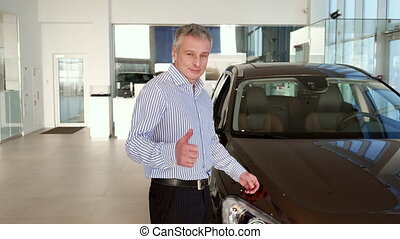 Mature man shows thumb up near the car at the dealership -...