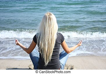 Woman in lotus position relax near the sea