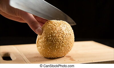 Cutting the bun with sesame seeds with a kitchen knife on...
