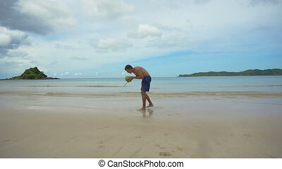 Man drinks coconut juice from a nut on a beach at the ocean....