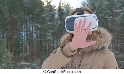 Woman uses a virtual reality glasses in winter forest....