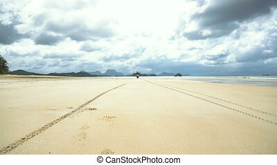 Man driving a motorcycle on beach. - Man on a motorbike on...