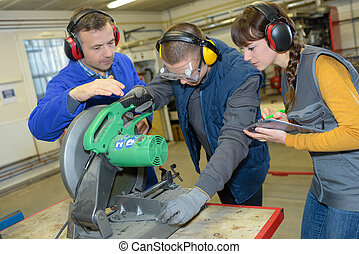 student in ironworks class using circular saw