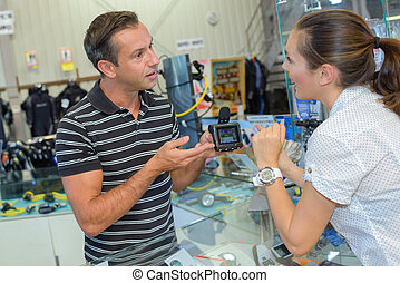 Female customer enquiring abut electronic device in shop
