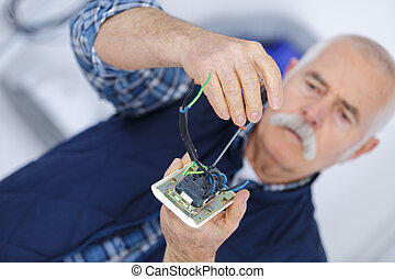 an older male repairing electronic equipments