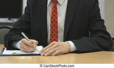 Man writing the text using a ball point pen - Man sitting at...