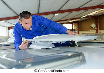 Mechanic fitting satellite receiver to roof of camper van