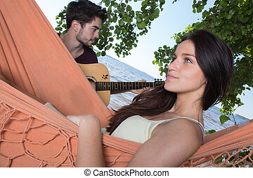 beautiful girl relaxing in hammock listening her boyfriend...