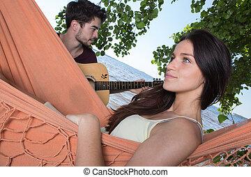 beautiful girl relaxing in hammock listening her boyfriend...