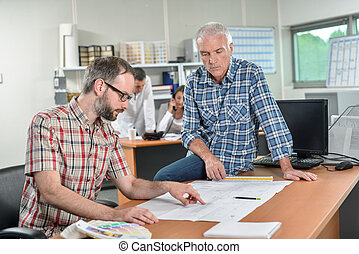 Two men looking at paperwork, one sat on the table