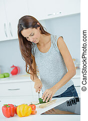 Woman at home chopping vegetables